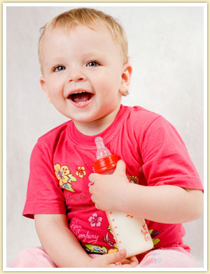 cute toddler holding a bottle of milk while smiling